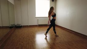 Female dancer training dance while rehearsing in dance studio. Elegant attractive female dancer improvising contemporary style dance while rehearsing in dance stock images