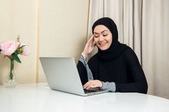 Elegant attractive muslim woman using mobile laptop searching online shopping information in living room at home stock photo