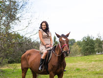 Elegant attractive woman riding a horse meadow. Elegant attractive woman riding a horse farm Royalty Free Stock Photo