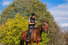 Elegant attractive woman riding a horse meadow Stock Photography