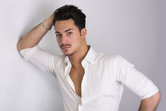Elegant attractive young man with white shirt. Leaning against wall royalty free stock images