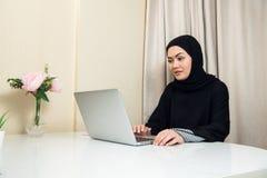 Elegant attraktiv muslim kvinna som använder den mobila bärbara datorn som hemma söker online-shoppa information i vardagsrum arkivfoto