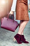 Elegant autumn outfit. Fashionable Caucasian boho woman wearing velour brown skirt, ankle suede marsala red boots with fringe and holding leather bag Stock Image