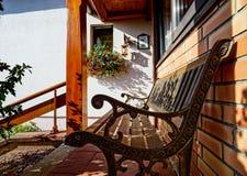 Elegant bänk nära huset, solig dag Arkivbild