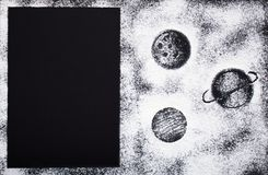 Elegant baking card with drawings of planets made of white wheat flour on a contrasting black background stock photos