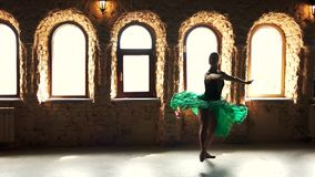 Elegant ballerina exercising in dance studio. Beautiful ballet woman in green dress working out in ballet studio, slow motion stock video
