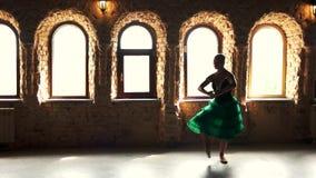 Elegant ballerinas dance in ballet studio. Slow motion beautiful dancer in green dress dancing in fashion studio on windows background stock video