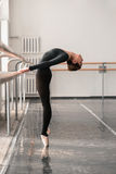 Elegant ballet dancer rehearsal in class. Elegant female ballet dancer rehearsal on barre in class, barrre and white wall on background royalty free stock image