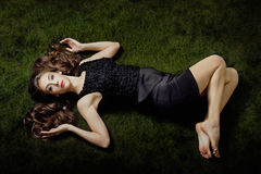 Elegant barefoot woman. Beautiful young elegant barefoot woman lie on grass, small amount of grain added stock images
