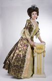 Elegant baroque woman. Elegant woman and a baroque style column Royalty Free Stock Photography