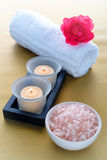 Elegant Bath Salts and Candles in a Spa. Aromatic bath salts in a ceramic bowl with burning candles in frosted glass holders and rose flower on a soft white Stock Photo