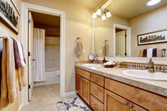 Elegant bathroom interior with large mirror, granite counter top and tile floor. Royalty Free Stock Images