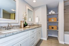 Elegant bathroom with long white vanity cabinet. Granite counter top, two sinks and built in shelves stock images