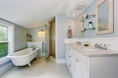 Elegant bathroom in pastel blue tones with white bath tub in the corner. Royalty Free Stock Images