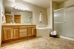 Elegant bathroom in soft tones with hardwood cabinets and marble tiled floor. Royalty Free Stock Photography