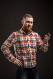 Elegant bearded man holding smoking pipe. Portrait of handsome bearded man in checked shirt smoking pipe. Studio shot. Isolated Stock Photography