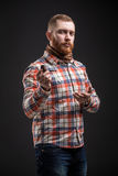 Elegant bearded man holding smoking pipe. Portrait of handsome bearded man in checked shirt smoking pipe. Studio shot. Isolated Royalty Free Stock Photos