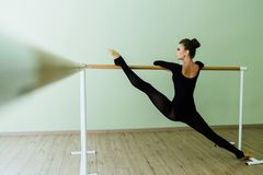Elegant beautiful ballerina with a perfect body doing stretching exercise. Elegant beautiful ballerina with a perfect body doing stretching twine exercise with Stock Photography