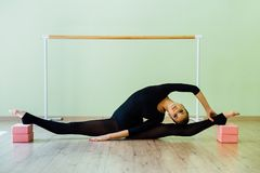 Elegant beautiful ballet dancer girl with perfect body sits on the floor. Elegant beautiful ballet dancer girl with perfect body sits on the floor on on twine Royalty Free Stock Photos