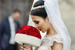 Elegant beautiful brunette bride walking down old european stree Stock Photos
