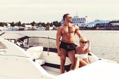 Elegant beautiful couple on boat in a swim wear royalty free stock image
