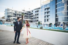 Elegant beautiful couple posing near modern glass building.  royalty free stock image