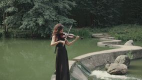 Elegant beautiful girl in black dress plays violin staying on bridge outdoors stock video footage