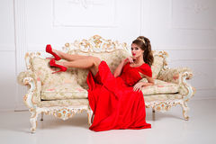 Elegant beautiful girl in a long red dress and shoes lies on a v Royalty Free Stock Photos