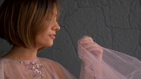 Elegant beautiful girl in a pink dress. Adult girl with short hair smiles, laughs and flirts.  stock video footage