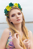 Elegant beautiful sexy girl in a wreath of flowers with bright makeup in the desert Stock Images