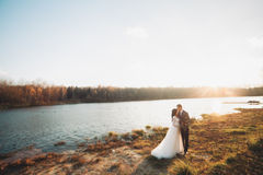 Elegant beautiful wedding couple posing near a lake at sunset Stock Image