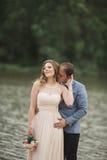 Elegant beautiful wedding couple posing near a lake at sunset.  Royalty Free Stock Photography