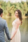 Elegant beautiful wedding couple posing near a lake at sunset.  Stock Images