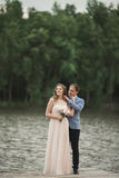 Elegant beautiful wedding couple posing near a lake at sunset.  Royalty Free Stock Photo