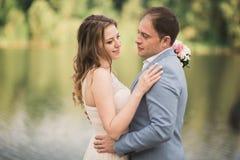 Elegant beautiful wedding couple posing near a lake at sunset.  Stock Image