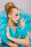 Elegant beautiful woman in a blue gauze ruff. And her blond hair in a neat bun in a sensual pose with closed eyes and a serene expression Stock Images