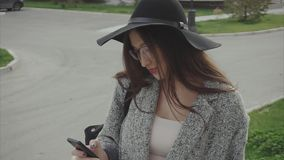 Elegant beautiful woman in hat and glasses texting on smartphone in the city. Outdoor stock video footage