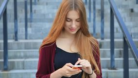 Elegant beautiful woman with long hair texting on smartphone in the city at sunrise. Wears red coat and black jeans stock footage
