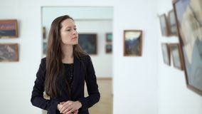 Elegant beautiful woman looks at the paintings in gallery during art opening reception. Pictures in the museum of modern. Art. Work of art paintings on the stock video