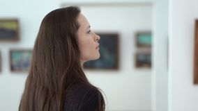 Elegant beautiful woman looks at the pictures in the museum of modern art. Close-up young girl watching photos in the. Photo gallery. Work of art paintings on stock footage