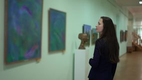 Elegant Beautiful Woman Looks at the Pictures in the Museum of Modern Art. Work of Art Paintings on the Exhibition at. Elegant Beautiful Woman Looks at the stock footage