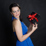 Elegant beautiful woman presenting a gift box Stock Photos