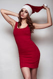 Elegant beautiful woman in a red dress and christmas hat Stock Image