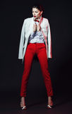 Elegant beautiful woman in red pants holding white coat Royalty Free Stock Photo