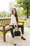 Elegant beautiful woman sitting on bench in the street. Stock Photos
