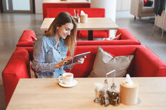 Elegant beautiful woman with tablet computer drinking tea at cafe Stock Photo