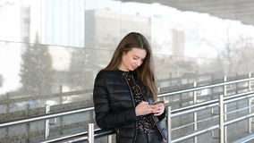 Elegant beautiful woman texting on smartphone in the city. Elegant beautiful woman texting on smartphone stock footage