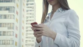 Elegant beautiful woman texting on smartphone in the city. Happy brunette teen girl with smile and cellphone. Text for communication in social network by stock video