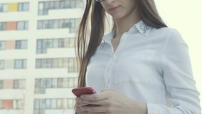 Elegant beautiful woman texting on smartphone in the city. Happy brunette teen girl with smile and cellphone. Text for communication in social network by stock video footage