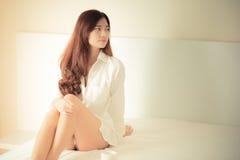 Elegant beautiful woman wearing white shirt posing in bedroom, Stock Image